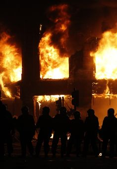 London riots - Police officers wearing riot gear walk past a burning building in Tottenham, north London August 7, 2011.