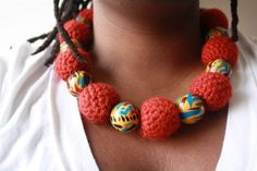 """This hand painted and crocheted necklace is a must have piece for your jewelry collection and is made of 8 abstract hand painted wooden beads in a mustard yellow base paint. Shades of red, blue, green and black adorn the surface. 9 hand crocheted beads in BRICK make this piece one of a kind and a definite head turner. It is one of my most versatile pieces as it is fully adjustable up to 18"""" long ... So wear it as short or as long as you like!  Include a clear drawstring attachment in the…"""