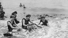 August 1916: Bathers collecting seaweed on the beach at Aberystwyth, Cardiganshire. (Topical Press Agency/Getty Images)