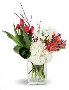 A soft display of spring blossoms including tulips, hydrangea and alstromeria. Colors