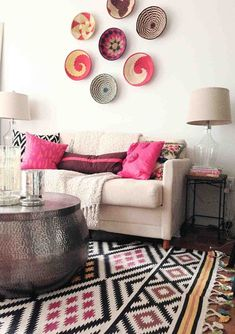 Light room, neutral furniture with the rug, pillows and wall decor providing ethnic touches.
