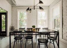 Ściany z cegły pomalowane na biało, czy to dobry pomysł? W tym przypadku zdecydowanie TAK! Zestawienie jasnych ścian z ciemnymi meblami stołowymi w jadalni oraz  z wyrazistą fakturą szafek w kuchni prezentuje się znakomicie.