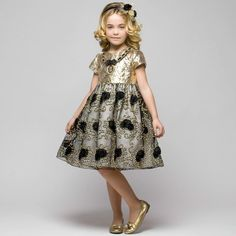 Girls gorgeous dress by Graci, ideal for a special occasion. It has a gold lamé bodice with capped sleeves and a velvet, chain anddiamantépendent necklace detail. The skirt is made with a top layer of black tulle decorated with tulle roses and gold coloured embroidered thread, over a layer of silky ivory fabric. It has a cotton feel lining with a tulle frill which gives it a lovely flared and voluminouslook.