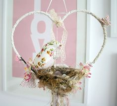 Heart shaped, handmade bird themed dream catcher serves as baby crib mobile in a baby girl nursery