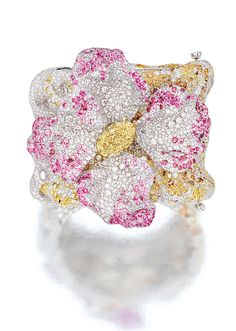 DIAMOND AND GEM-SET 'AZALEA' BANGLE, CINDY CHAO. Modelled as an azalea, set in the centre with an oval fancy light yellow diamond weighing 7.02 carats, the petals decorated with brilliant-cut diamonds, highlighted by circular-cut rubies, pink sapphires and rhodolites t mounted in 18 karat white gold, signed.