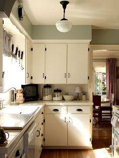 @Amy Fairchild Amy, this kitchen's cabinets remind me of yours. I could see something like this in your house until you can replace the ones you have! The green was the icing on the cake to make me think of you!   white cabinets + black hardware, drawer pulls, wall color, GINGHAM CURTAINS