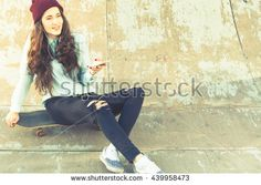 Hipster skateboarder girl with skateboard outdoor. Using mobile phone and listen to music. Headphones. Skatebord at city street. Cool, Funny Tenager. Halfpipe. Skateboarding at Summer. Schoolgirl