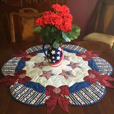"~36"" diameter. Stars and stripes forever adorn your table with patriotic love. Machine applique as you quilt makes this a quick project. Dimensional bow ties add the perfect finish. Sample uses Northc"