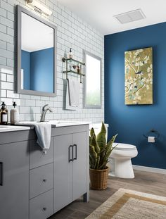 Give your bathroom a cosmopolitan edge. Stylish elements like a subway-tile wall and cement gray vanity look like they belong in a sophisticated downtown apartment. Add a pop of personalized color with an accent wall and modern artwork. Panel flooring and a plant stay humble.