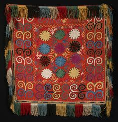 """TENT DECORATION (ILGITSH)  UZBEKISTAN KUNGRAT PEOPLE c. 1890 fine silk chain stitch embroidery on red wool; 23' X 23"""" unusual border design condition: Overall very good except some areas of the black embroidery of the flower heads in the field show wear"""