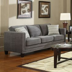 Sofa with nailhead trim and two throw pillows.   Product: SofaConstruction Material: Polyester and hardwood...