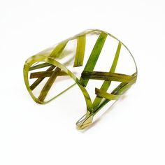 This wide cuff bracelet features pressed grass that is encased in eco resin. It…
