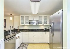 Kitchen - AFTER renovation - new light; new appliances; new hardware; granite counters; sink; flooring; paint