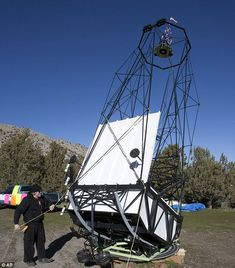 Impressive: Mike Clements stand with his homemade 70-inch telescope in Herriman, Utah. While the primary mirror is 70 inches, the black metal structure itself stands about 35 feet tall, supporting a secondary mirror that is 29 inches
