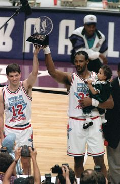 Utah Jazz teammates and co-Most Valuable Player winners John Stockton, left, and Karl Malone hold up the All-Star MVP trophy after playing for the West team, which won the 43rd NBA All-Star game, 135-130, in Salt Lake City, Sunday, Feb. 21, 1993.  Malone holds his daughter, Kaydee.  (AP Photo/Roberto Borea)