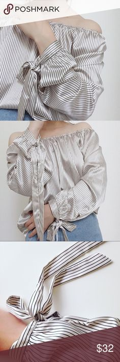 """NWT ivory metallic-shiny stripe off-shoulder top Brand New Boutique item.  Thin and air-light off-shoulder top.  Ivory with black stripes.  Fabric is smooth and metallic-shiny.  Bow-tie on sleeves.  100%poly.   True to size.  Chest: S-38"""", M-40"""", L-42"""".  Length approx 25"""".   Made in USA  NO trade SmilingBear Tops"""