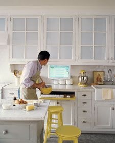 What's better in this kitchen: the computer in the kitchen - keyboard drawer or the fact that the man is cooking?