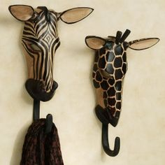 """The Exotic Tribe Zebra and Giraffe Wall Hook Set is a rare treasure, evoking the wild majesty of the savannah and the noble creatures that call it home. Handcarved in Kenya by Akhamba tribesmen, these unique safari animal wall hooks are skillfully fashioned from tropical Neem wood. Handpainted wall accents have a black hook on the bottom. Each is approx. 8.5""""Wx12""""H.    •Two-piece animal wall masks set (zebra and giraffe)  • African wall Masks are handcrafted in"""