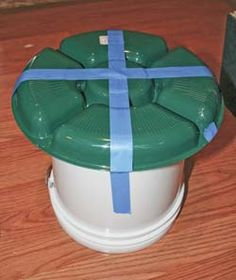 A cheap and easy chicken feeder made from a 2 gallon bucket and a relish dish found at the Dollar Store. Picture shows the tray taped in place prior to drilling fastening holes