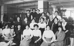 "Women garment workers assemble with a few men for a group portrait. A ""No Smoking"" sign in English and Yiddish is posted in the work space.  