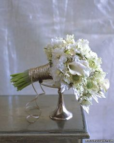 Cone-shaped bouquet with miniature calla lilies, Scabiosa, Delphinium florets, and lilies of the valley.