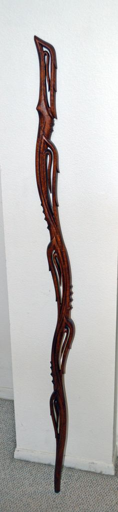 Vine and Thorns walking stick. This took me over 2 years to finish as I gave up on it twice, finally had it to about 80% and said the heck with it and kept my head down and got it done. Most difficult piece I've carved, a complex variation on my original leaves and vine walking stick. Made from a piece of figured Sapele. Finished with Teak Oil.