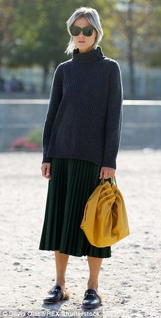 A cool member of the public was snapped at the Paris fashion shows, teaming a long roll neck jumper with the 'it' pleated midi skirt and luxurious fur-lined Gucci loafers. Completing the look is a head of grey hair