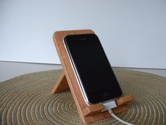 Unique Oak Wood Holder for iPhone, iPod Touch, and other smart phones. Each one hand made, and hand finished with polyurethane satin finish. Holder has attractive brass hinges, and folds up for transport. Very sturdy, and non-slip footing allows use of touch screen while seated in holder. Cut-out in the base allows Apple devices to be charged while setting upright in holder. One of the few stands that lets you use the device touch screen without tipping over!   Thin and sleek like your Apple…