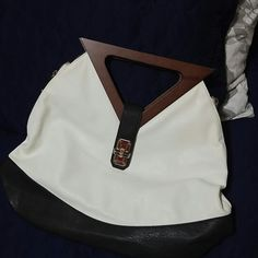 """Two Tone Shoulder Bag w/ Wood Handle Two Tone Shoulder Bag w/ Wood Handle includes Cross Body Strap as well. I used this bag for one day and its been in my closet since.  This bag has 3. Pockets: one large main pocket with 2 smaller pockets inside.  One of those has a zipper. There is also a zipper outside. The main pocket has a zipper closure and 2 others on each side with a buckle as well. It is a large bag: )  roughly 17"""" Length 13"""" Height 5"""" Deep. The handbag is CLEAN inside and is from…"""