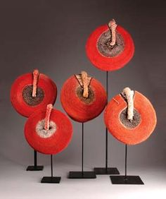 "Africa | Hats worn by married Zulu people of South Africa | Ring-shaped base of plant fibre is coated with red dyed fabric which is sewn with twisted cords, arranged concentrically, a ""tail-like"" appendage on top"