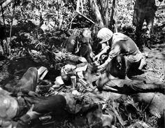 February 1944: A wounded marine receives treatment from a Navy medical corpsman at a jungle first aid station behind the lines on New Britain Island, New Guinea, in the Battle for the Strategic Japanese air field on Cape Gloucester during World War II.