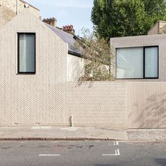 Pale bricks are arranged in a herringbone pattern on the outer walls of this house in London that architect Zoe Chan designed and built for herself.