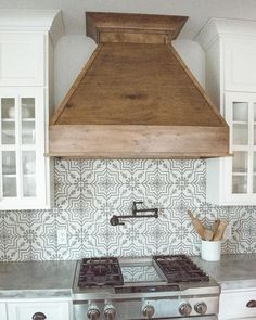 Pattern kitchen backsplash and wooden hood