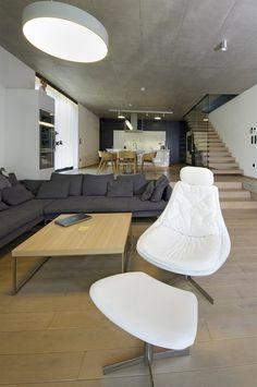 Optické oddělení kuchyně s jídelnou podtrhuje dvojúrovňová podlaha. Tři výškové stupně pohledově navazují na monolitické schodiště, jehož nášlapné plochy mají, stejně jako podlaha, krytinu z běleného dubu.