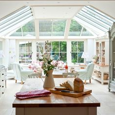An open-plan conservatory design allows for a seamless join between kitchen and dining space, bringing in plenty of light. Here the flat section of the roof reduces glare over the dining table.