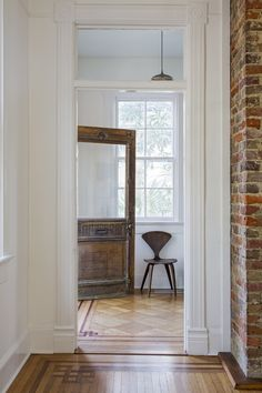 In the entryway, the original, 100-year-old carved wood door mixes with a chair by Bauhaus-educated designerNorman Chernerand a commissioned pendant light by third-generation woodworker Emily Brock of Board & Bread in Nashville. Mix-and-match wood pieces throughout add a naturalistic but sculptural feel.