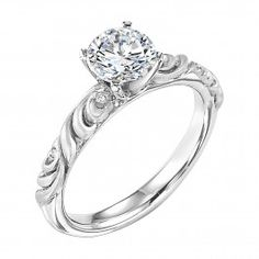 ArtCarved diamond engagement ring with round center stone and satin finished floral carving detail highlighted with diamonds.