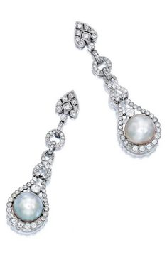 A Pair of Early 20th Century Natural Pearl and Diamond Pendant Earrings. Each set with a button-shaped natural pearl of slightly silver and slightly brown colour, suspending from links millegrain-set with circular- and single-cut diamonds, mounted in platinum. #BelleEpoque #Edwardian earrings
