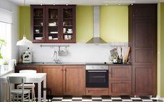 Traditionelt, mørkebrunt køkken med vitrinelåger, mørke bordplader og hvidevarer af rustfrit stål