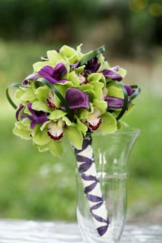 green and purple flower bouquet - plus straps of ribbon on handle?
