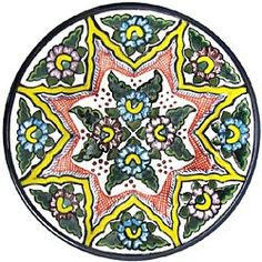 This beautifully handcrafted Talavera plate by the renowned Tomas Huerta ceramic studio will make a vibrant and cultural addition to any space in your home. With over 100 unique designs in this expansive collection, you're sure to find one that fits your taste. Each authentic Talavera plate is handmade in Puebla, Mexico, and is 100% lead free; chip and crack resistant; as well as microwave, oven, and dishwasher safe! There is even an eyelet on the back of every plate for easy wall hanging…