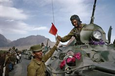 An Afghan army soldier hands a Soviet flag in solidarity to a departing soldier on the first day of the Soviet army's withdrawal from Afghanistan. May, 1988