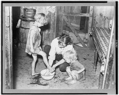 Mother washing children's feet in bowl during the Great Depression.