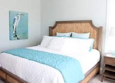 Simple airy coastal bedroom idea with a woven bed and shorebird art, featured on Completely Coastal.