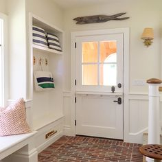 Beach house mudroom SWIPE for another view with Dutch door. Brick floors are my fave for charm and indestructibility, plus they hide everything. Large cubbies have plenty of room to hang damp towels and beach bags. #hilderbrandinteriors #LHcapecod #beachhouse #mudroom