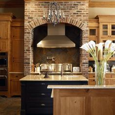 Brick stove hood and beautiful rustic kitchen designed by Ourso Designs.