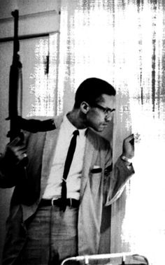 Malcolm X holding a M1 Carbine and peering behind a curtain in response to death threats against him and his family. 1964.   ()