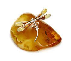 Malgorzata Wasowska Jewellery Company Amber and silver firefly resting on a piece of amber.