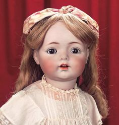 """Theriault's Large German Bisque Toddler,121,by Kammer and Reinhardt with Toddler Body 27"""" (69 cm.) Bisque socket head,brown glass sleep eyes,dark eyeliner,painted lashes,feathered brows,accented nostrils,open mouth,outlined shaded lips,two upper teeth,blonde (new) human hair wig,composition and wooden ball-jointed toddler body with side-hip jointing,antique costume. Condition: generally excellent. Marks: K*R Simon & Halbig 121 62"""
