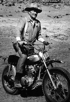 A new breed of horse, a Honda motorcycle, takes a little getting used to under a vintage cowboy like John Wayne.